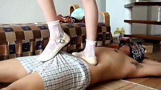 Attractive Japanese girl punishes her slave with her feet