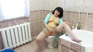 Brunette urinates and masturbates in the morning sitting on the toilet