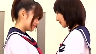 2 Schoolgirls Kissing Patting While Standing In The Classroo